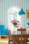 Esstisch mit Holzstühlen und blauer Polsterstuhl vor einem Rundbogenfenster
