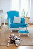 Blauer antiker Armstuhl mit Hocker auf Teppich, Dalmatiner liegt auf dem Teppich im Vordergrund