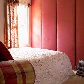 Schlafzimmer mit stoffbezogenem Schrank, Doppelbett mit Tagesdecke und Fenster mit gemusterten Vorhängen