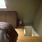 Schlafzimmer im Dachgeschoss mit Treppenaufgang, Bett und Dachfenster, grünen Wänden und Holzboden