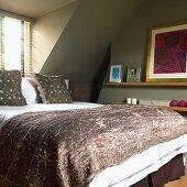 Schlafzimmer im Dachgeschoss mit Fenster, grünen Wänden, Doppelbett, Wandregal und modernen Bildern