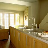 Küche im Landhausstil mit pastellgrünen Wänden, Holzmöbeln und Mittelblock mit Spülbecken