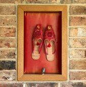 Orientalische Schuhe als Wanddeko in einem Holzrahmen an einer Ziegelmauer
