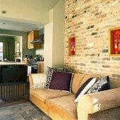 Zimmerflucht in einem Landhaus: Wohnzimmer mit Sofa an einer Ziegelwand, Küche mit Mittelblock und Essecke