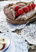 Crocheted doilies tied together as mat on stone underneath wooden board of bread and vine tomatoes