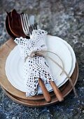 Cutlery tied up in lace doily on stack of plates and wooden boards