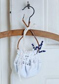 Coat hanger with lavender flowers in white, crocheted bag hanging from key in old door