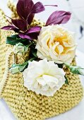 Arrangement of feathers and roses of the varieties 'Lady Hillington' and 'Eifelzauber' in raffia bag