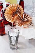 Wheels of folded newspaper decorating a drinks glass