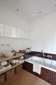 Waschschüssel auf Holzplatte unter modernem Spiegelschrank und Badewanne