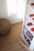 Blick von Treppe auf weissen Regalschrank mit roten Vintage-Spielzeugautos
