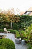 Garten mit rustikaler Holzliege auf gepflastertem Weg und formgeschnittenen Hecken