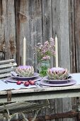 Place settings with candles in artichoke flowers and flowering marjoram in preserving jar