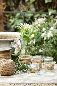 Hand-knitted covers for glass vases & tealight holders on garden table