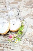 Donuts decorated with white icing and flowers on glass plate with glass cover