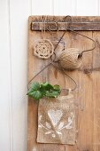 Jute yarn reel and white-painted sacking bag hanging from wire hangers on old wooden panel next to doily crocheted from jute yarn