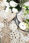Doilies hand-crocheted from jute yarn and hessian heart next to doughnut and chamomile on metal cake stand