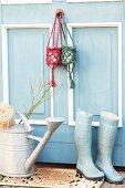 Small hanging baskets hand-crocheted from jute yarn hanging on blue and white country-house door above zinc watering can and wellington boots
