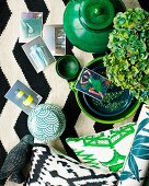 Arrangement of various ceramic pots, green ornaments and photos on black and white rug
