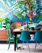 Dining table, various chairs and spherical glass lamps in front of jungle patterned wallpaper