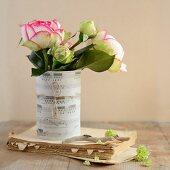 Weisse Rosen in einer Notenblattrolle auf altem Buch