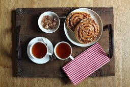 Plate of nut pastries, cups of tea and sugar crystals on wooden tray with hand-stitched leather handles