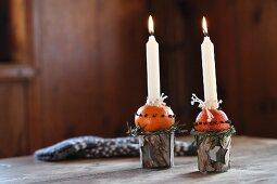 Adventlich selbstgebastelte Kerzenständer aus Bechern und Orangen mit Nelken gespickt
