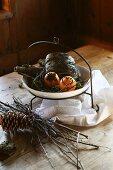 Adventlich gespickte Orangen auf Schale mit Metallhängegestell neben Reisig und Tannenzapfen auf Tisch
