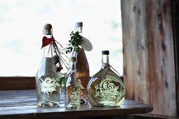 Mit Ornament, Anhängern und Bändchen als Geschenk verzierte Wein- und Sektflasche