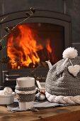 Becher mit Strickbordüre neben selbstgehäkelter Warmhaltehaube auf Tisch vor Kaminfeuer