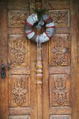 Hand-made, festive wreath on carved wooden door