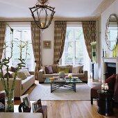 Klassische Sofagarnitur und Couchtisch mit Metallgestell auf hellem Teppich vor Fenstertüren und beige gestreiften Vorhängen