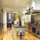 Free-standing island counter in illuminated fitted kitchen with stainless steel fronts