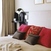 Scatter cushions on double bed with upholstered headboard in modern bedroom