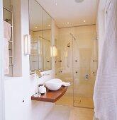 Designerbad mit kleinem Waschtisch auf Holzplatte vor verglastem Duschbereich