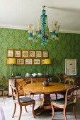 Dining area with antique, English furniture, chandelier & floral patterned wallpaper