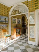 Entrance hall of English country manor house with diagonal, chequered marble floor tiles and gallery of pictures on patterned wallpaper