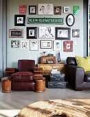 Leather armchair below collection of signs & pictures on wall