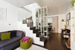 Offener Wohnraum mit hoher Regalwand als Raumteiler und Blick auf dunkelbraune Treppe mit Glasgeländer; davor eine graue Couch und ein grüner Sitzsack