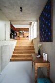 Vintage Wandtisch und moderne Kunst an Betonwand; im Hintergrund eine helle Holztreppe und ein großer Bücherschrank