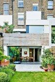 Blick auf modernen Wohnraum mit verschiebbaren Glastüren und traditioneller Hausfassade im Hintergrund