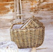 Two hand-woven willow baskets in front of wooden wall
