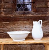 Hand-made pottery washbasin and jug on wooden bench against historical wooden facade