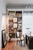Antique desk and chair in front of partially open-fronted shelving in traditional study