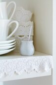 Edge of kitchen shelf decorated with lace ribbon; napkin rings of starched lace trim in background