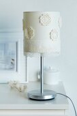 Table lamp lampshade decorated with flower-shaped sections of crocheted doily and gossamer-thin lace trim