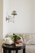 Runder, schwarzer Beistelltisch mit Vintage Telefon vor hellem Sofa an Wand und Retro Wandleuchte mit Metallschirm