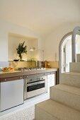 Blick über offene Treppe auf moderne Küchenzeile mit beleuchteter Wandnische
