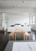 Tisch und Bänke aus hellem Holz auf grauem Estrichboden vor weiss gehaltenem Schlafbereich in loftartigem Raum