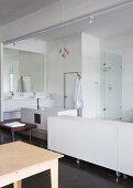Weisses Sideboard auf Rollen neben offenem Waschbereich in loftartigem Raum